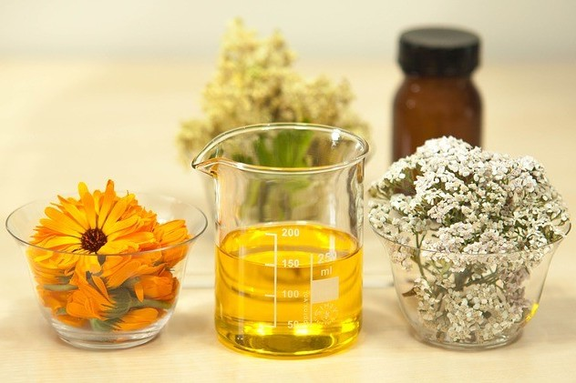 measuring cup with jojoba oil and its flowers