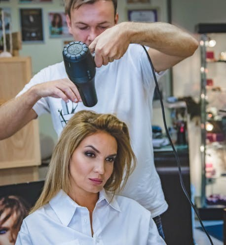 hairdresser using hair blow dryers on a customer