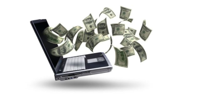 laptop with money flying out